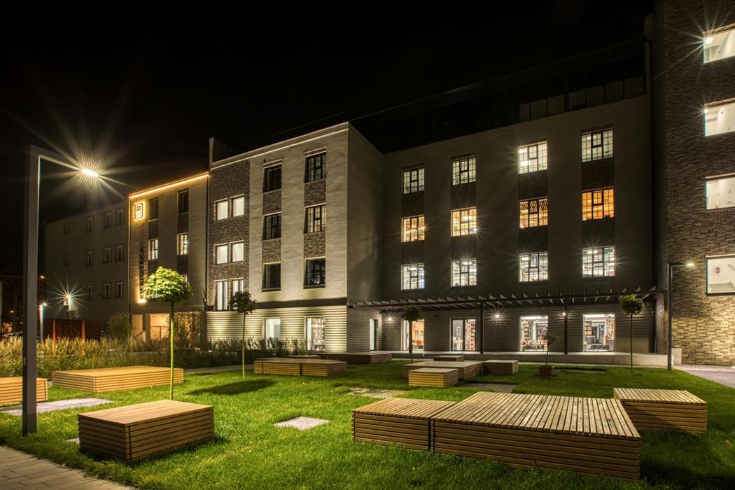 Nowa siedziba Miejskiej Biblioteki Publicznej w Żorach w historycznym budynku dawnego młyna elektrycznego. Widok nocny. Na pierwszym planie oświetlony, nowoczesny plac z trawnikiem i drewnianymi podes