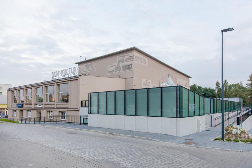 Modernizacja Miejskiego Domu Kultury Kazimierz w Sosnowcu. Na pierwszym planie wybrukowana ulica . W centralnej części odrestaurowany budynek, elewację zdobią obrazy wyrzeźbione w tynku. Po prawej prz