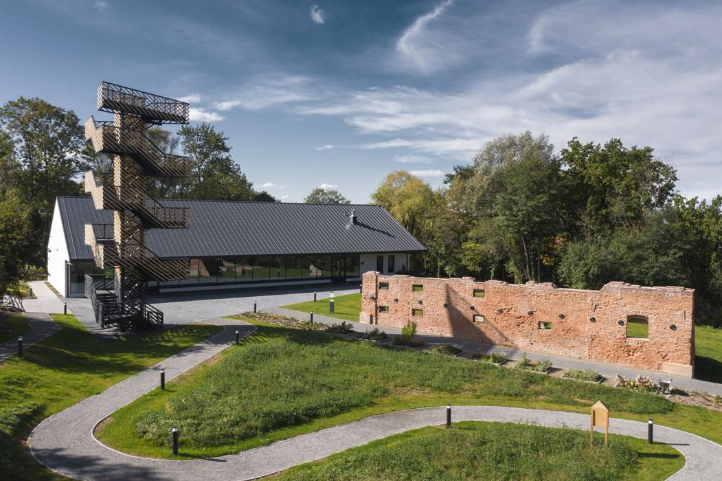 Centrum Edukacji Ekologicznej wraz z zagospodarowaniem Potoku Czechowickiego. Po lewej stronie ażurowa wieża widokowa, po prawej ceglane ruiny dawnego spichlerza, w tle budynek Centrum z dwuspadowym c