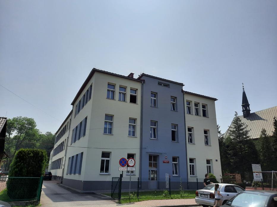 Rozbudowa budynku Szkoły Podstawowej nr 1 im. Mikołaja Kopernika w Porąbce. Dwupiętrowy budynek szkoły z jasną elewacją i spadzistym dachem.