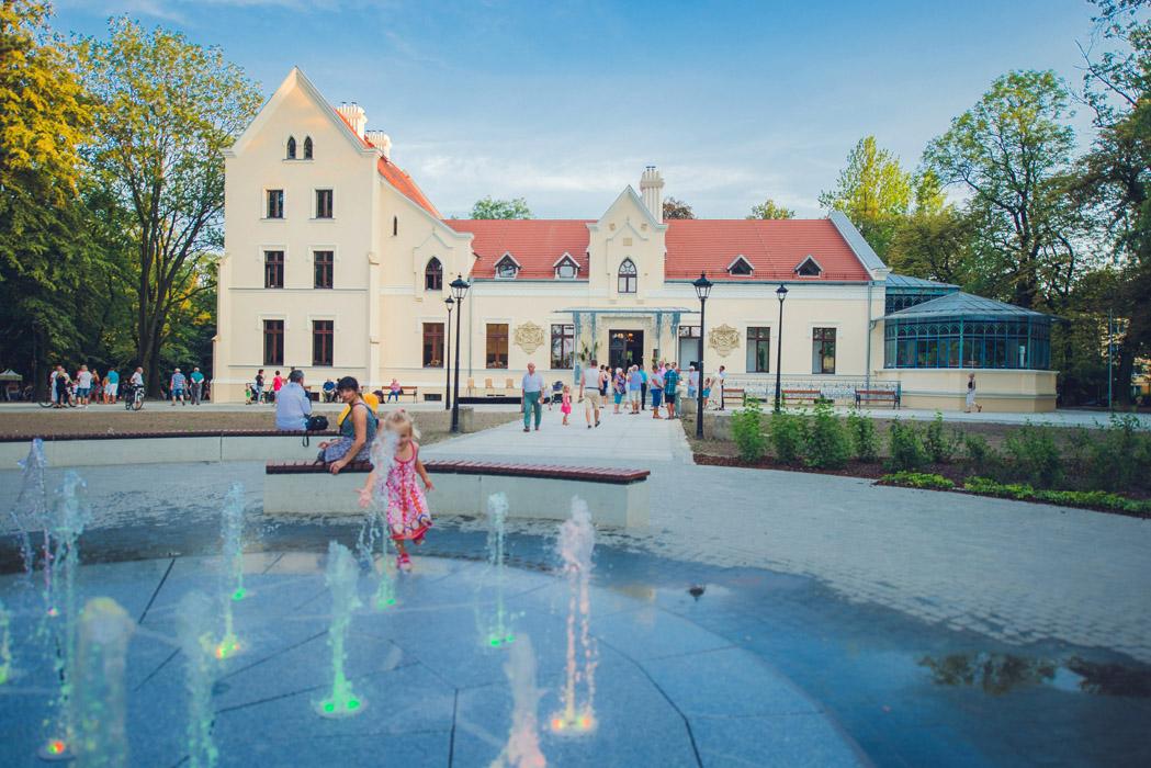 Pałac Rheibabenów zwany Zameczkiem. Widok od frontu, na pierwszym planie fontanna z tryskającymi  z posadzki podświetlonymi kolorowo strumieniami wody. W tle Zameczek ze szklaną 8-boczną oranżerią po
