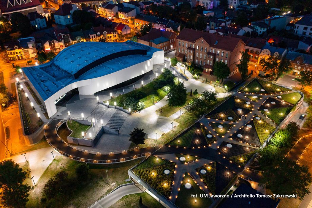 Hala Widowiskowo-Sportowa w Jaworznie. Zdjęcie zrobione w nocy w ujęciu z lotu ptaka. Z lewej strony podświetlony budynek hali i jego przedpole z alejkami i zielenią towarzyszącą. W tle widoczne okoli