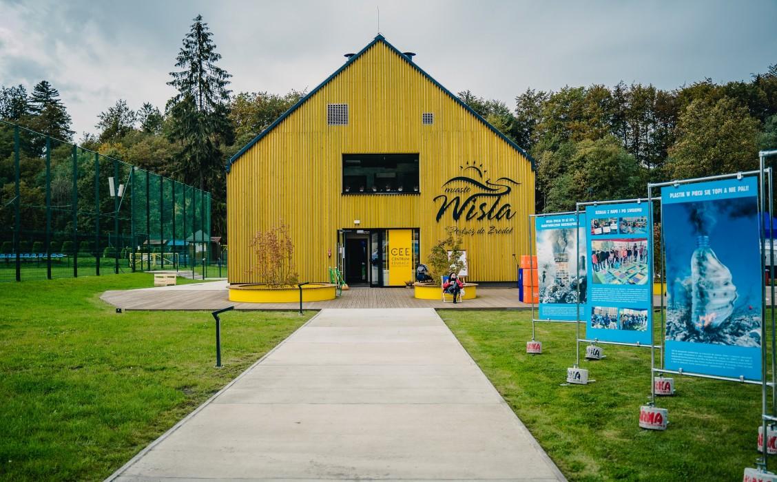 Centrum Edukacji Ekologicznej w Wiśle. Na pierwszym planie ścieżka prowadząca do wejścia do jasnego budynku z dwuspadowym dachem. Po prawej stronie na trawniku tablice informacyjne, po lewej trawnik, w tle wysokie drzewa.