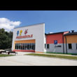 Budowa przedszkola publicznego w Gołkowicach, gmina Godów. Na pierwszym planie parking  z miejscami dla uprzywilejowanych. W głębi budynek przedszkola z wesołymi, kolorowymi dekoracjami na elewacji, ł