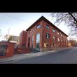 Centrum Usług Społecznych w Zabrzu. Kompleksowa rewitalizacja budynku gazowni z 1870 r. wraz z terenem przyległym. Widok na 3 piętrowy klinkierowy budynek z mocno wysuniętym okapem dachu. Na pierwszym