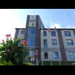 Budynek użyteczności publicznej w Świerklanach. Widok na główne wejscie do budynku, nad wejsciem umieszczony jest herb gminy, powyżej herbu nazwa urzędu i zegar. Po lewej stronie kwitnące kwiaty, na t