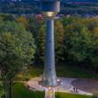Nitowana wieża ciśnień w Będzinie-Grodźcu. Wieczorny widok z lotu ptaka na oświetlony teren wieży ciśnień. W centrum podświetlona nitowana, wysoka wieża w kształcie zadaszonego kielicha. Przed wieżą s