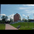 Rekultywacja i remediacja terenów dawnej koksowni Orzegów. Na pierwszym planie piesza ścieżka, trawnik, ławka oraz młode drzewa. W tle, na wzniesieniu, wysoka ceglana budowla w kształcie prostopadłośc