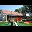 Przedszkole Gminne w Smolnicy, gmina Sośnicowice. Na pierwszym planie plac zabaw. W tle budynek  nakryty dwuspadowym dachem pokrytym dachówką oraz wysokie drzewa. Fotografia pochodzi ze zbiorów zgłasz