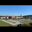Zagospodarowanie terenu po byłym PGR na potrzeby rynku miasta Radzionków. Na pierwszym planie płyta rynku z zielenią,rzeźbami, oświetleniem i zbiornikiem wody w kształcie litery L. W tle budynki, wież