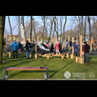Podlesie Pełne Życia w Dąbrowie Górniczej. Widok na trawiasty plac z bawiącymi się dziećmi na drewnianych urządzeniach, w tle widoczny ziemny nasyp ze zjeżdżalnią oraz drzewa, na pierwszym planie ławk