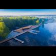 Przystań kajakarska MOSM w Tychach. Widok z lotu ptaka. Na pierwszym planie lustro wody, w centralnej części obiekty drewnianej przystani z pomostami i siedziskami w formie amfiteatralnej. w tle wysok