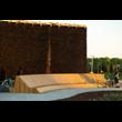 Ławki przy tężni solankowej w Tychach. Na tle wysokiej, ciemnej tężni widoczna jasna, drewniana bryła ławki z długim, dwustronnym siedziskiem i oparciem, usytuowana na utwardzonej nawierzchni, po lewe